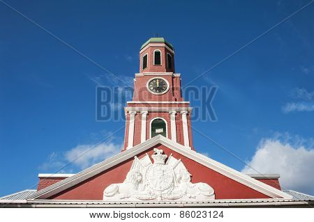 Famous red clock tower on the main guardhouse at the Garrison Savannah. UNESCO garrison historic area Bridgetown, Barbados poster
