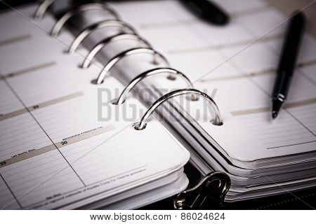 Personal Organizer Or Planner With Pen On White Background