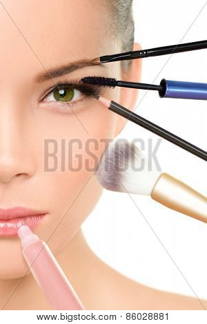 Makeup beauty transformation concept face makeover - Asian woman with many brushes against one side of the face putting mascara, blush and lip gloss
