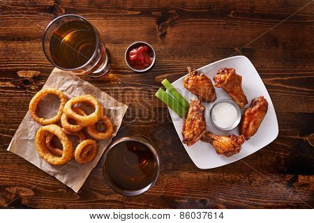 appetizer sampler with onion rings and chicken wings shot top down