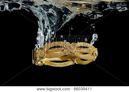 elaborate gold bracelet splashing in water against black poster