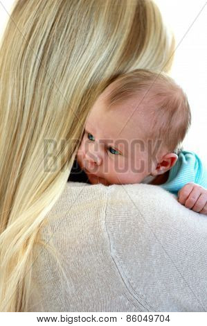 A young blonde mother is seen from the back holding a newborn baby girl over her shoulder burping her after feeding. poster