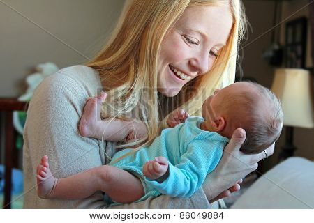 Young Mother Smiling At Newborn Baby In Home Nursery