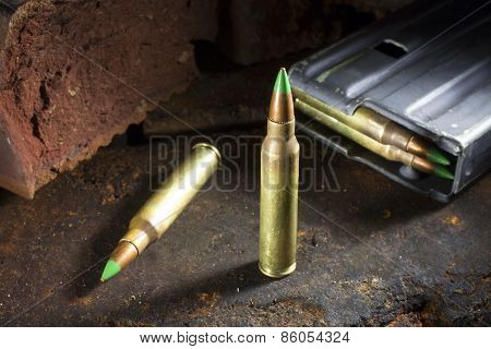 Small rifle ammo with green tips and a loaded magazine behind poster