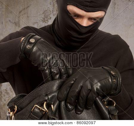 Thief stealing money from women handbag