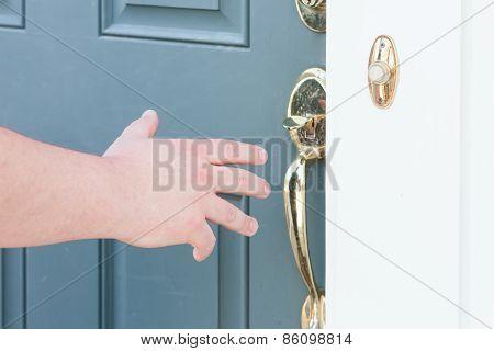 Man's Hand About To Open Front Door