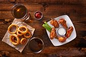 appetizer sampler with onion rings and chicken wings shot top down poster