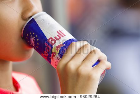 Asian girl drinks a cold can of Red Bull Energy drink