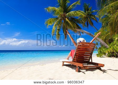 happy woman sitting on beach chair at tropical beach