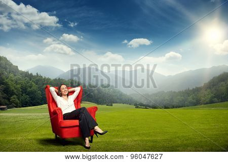 smiley young woman resting in red chair on the green meadow over beautiful landscape with hills, forest and sky