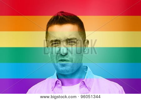 homosexual, homophobia, intolerance and people concept - gay man wrying over rainbow flag background
