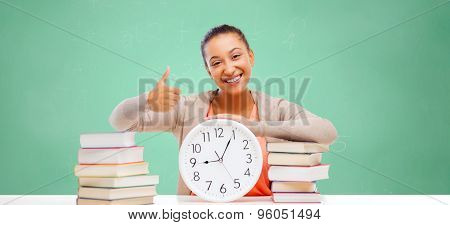 education, school, people and learning concept - afro american student girl with books and clock showing thumbs up over green chalk board background