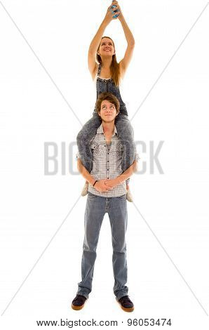 Woman sitting on mans shoulders while she assembles a blue lightbulb high up and he looks upwards sm