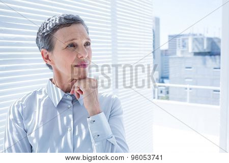 Businesswoman looking away with arms folded in the office