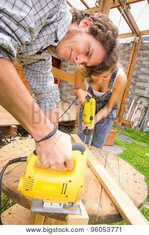 Couple working together on renovation project outdoors using a jigsaw and power drill
