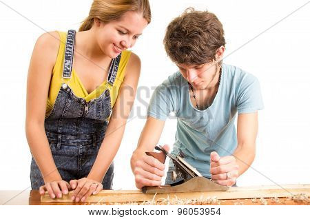 Couple working together as man is using manual hand plane tool on wooden surface while woman helping