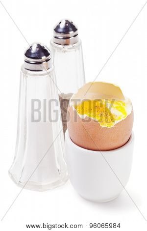 Cracked boiled egg in eggcup with salt and pepper shakers isolated on white background
