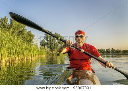 Senior male paddler is paddling a racing sea kayak on a lake along shore covered by reed