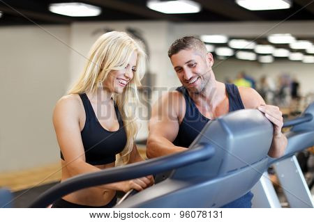 Personal trainer set difficulty on treadmill for blonde woman in gym poster