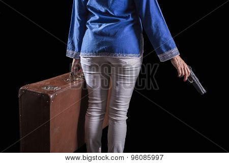Women with Islamic headscarf subject suitcase and gun