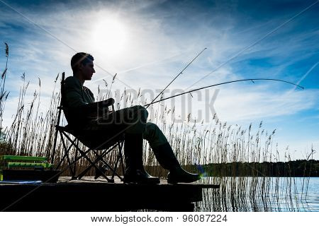 Fisherman or Angler at lake in Sunrise backlit, his body forming a silhouette