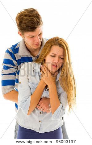 Couple demonstrating first aid techniques by man performing heimlich on female choking