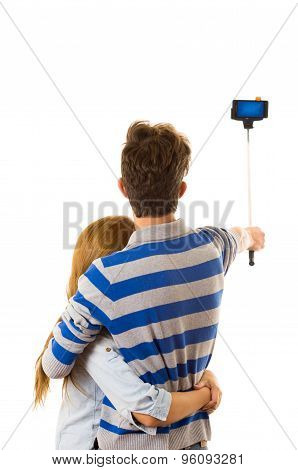 Couple with selfie stick posing for mobile back facing camera