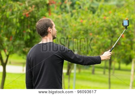 Hispanic man posing with selfie stick in park environment, shot from side profile angle