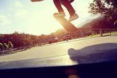 skateboarder legs doing a trick ollie at skatepark poster