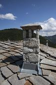 Vintage old stone authentic chimney on top of unique stone roof poster