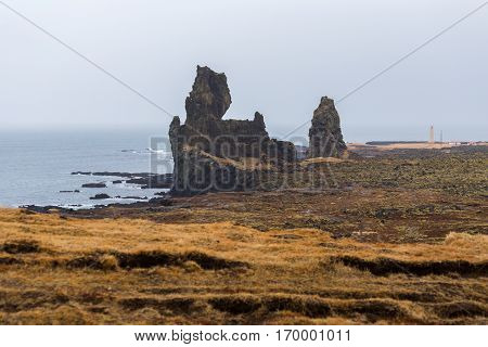 The cliffs at Londrangar a pair of basalt pinnacles rising from the coastline of the Snaefellsnes peninsula in Iceland. The rock formations remain from volcanic plugs after the softer outer layers of a crater eroded away by elements at the seashore.
