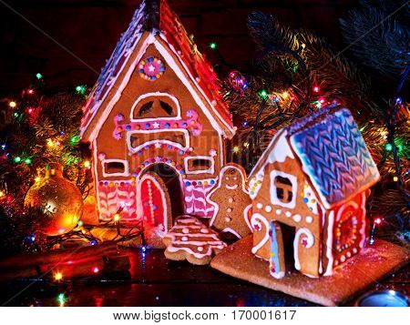 Gingerbread houses country with christmas lights string on wooden table. Close up Xmas cookies decorating christmas ball and tree. Light effect for festive dinner. Nobody on night picture