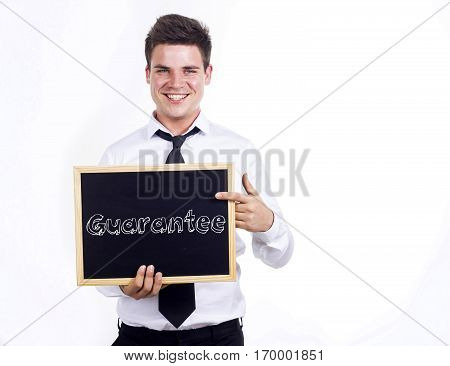 Guarantee - Young Smiling Businessman Holding Chalkboard With Text