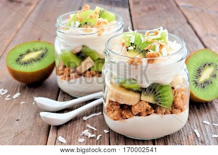 Healthy Kiwi, Banana, Coconut Parfaits In Mason Jars On A Rustic Wood Background