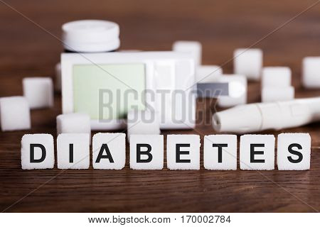Diabetes Kit And Sugar Cubes With Text Diabetes On Wooden Desk
