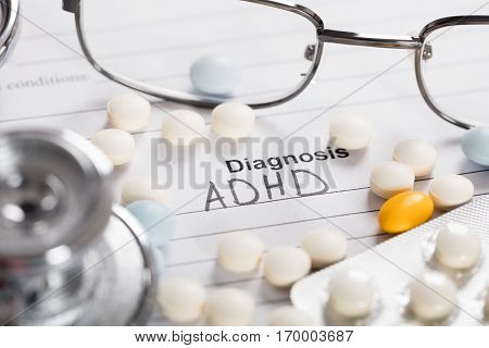 Pills;Glasses And Stethoscope With Text Diagnosis ADHD On Paper
