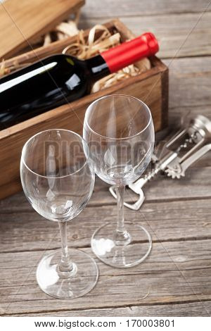 Red wine bottle and glasses on wooden table