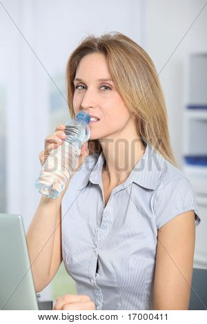 Closeup of beautiful office worker drinking water