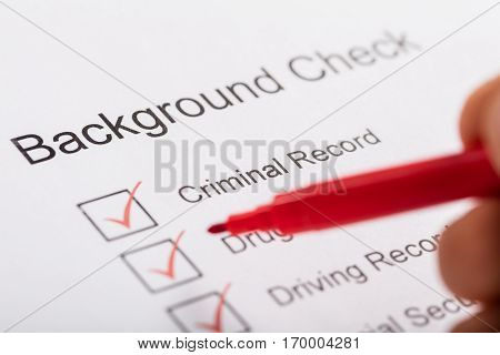 Close-up Of Person Hand Ticking Off Checkboxes In Background Check Form