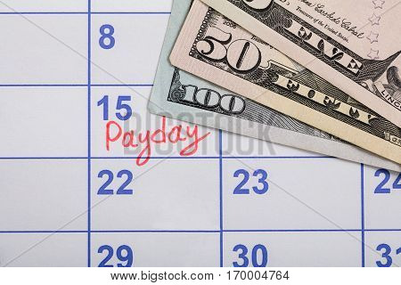 Close-up Of Pay Day Reminder On Calendar With Banknotes