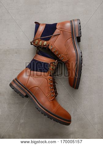 Men's accessories with brown leather boots on gray grunge background