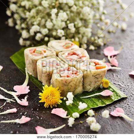 Chicken Maki Sushi - Sushi Roll made of Smoked Chicken Breast, Cheese, Cucumber and Tomato inside. Pancake outside. Sushi Served on Banana Leaf. Japanese Sushi Food and Natural Flower Concept
