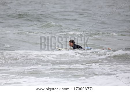 A young man in late teenage years surfing in the ocean. He is floating on his surfboard waiting for a wave.