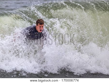 A young man bodysurfing in the ocean. His upper body is seen in the wave.