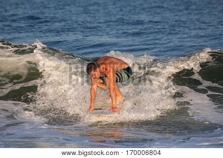 A young man in his early 20's surfing. He has caught a wave in the Atlantic Ocean. The location is the New Jersey Shore.
