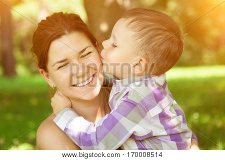 Mom and son. Child kisses his mother on nature background. Positive  summertime scene of love and tenderness. Mummy and baby in park