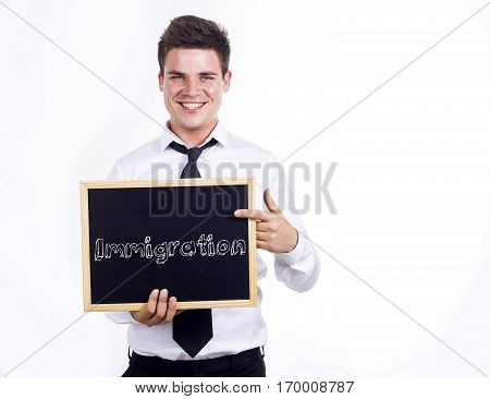 Immigration - Young Smiling Businessman Holding Chalkboard With Text