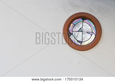 A round old fashion window in a white wall