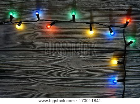 Christmas colorful garland lights on wooden rustic background.