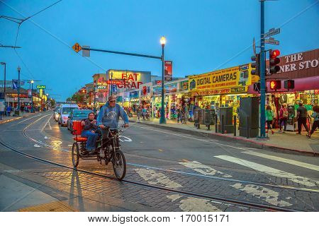 San Francisco, California, United States - August 14, 2016: rickshaws sightseeing tour on Jefferson rd at Fisherman's Wharf. Freedom concept. San Francisco street view at twilight.